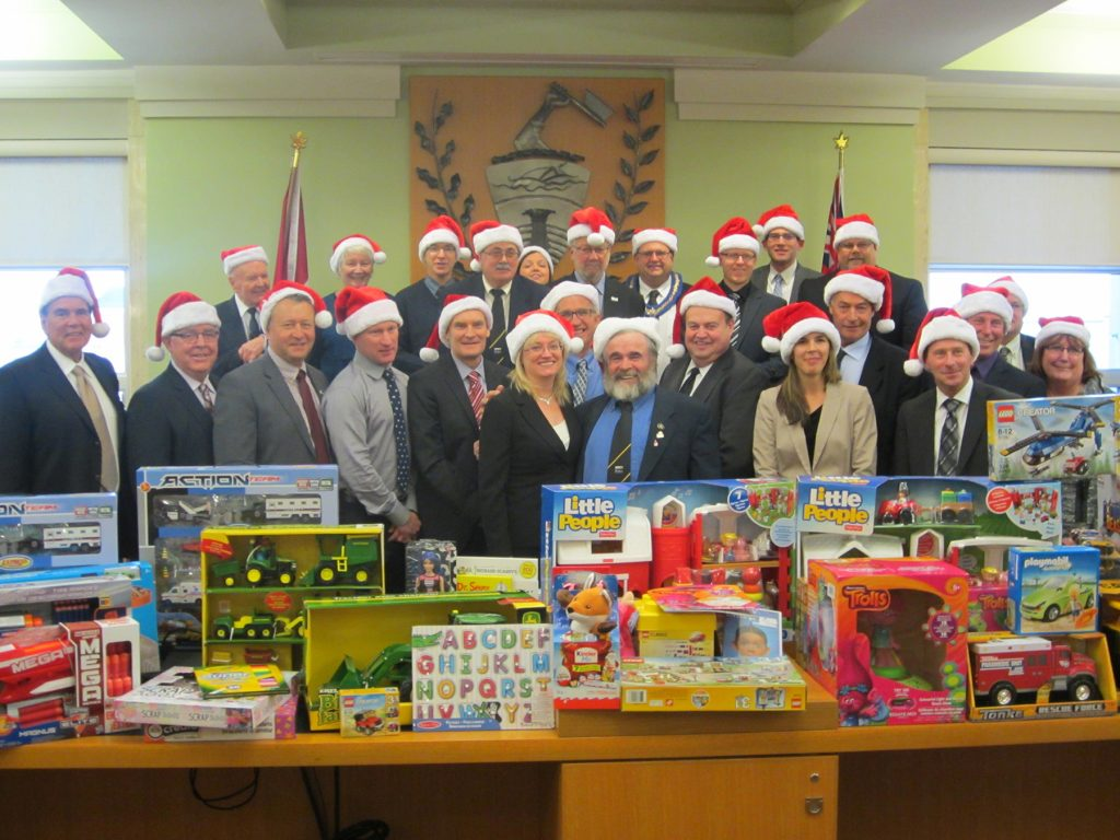 Boxes of toy tractors, lego, building blocks, doll house, and games are piled on top of desk in front of the smiling faces of councillors and senior staff