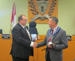 Warden Ginn and Past Warden Gowing exchange a handshake and a heartfelt moment of mutual respect in front of the council dais.