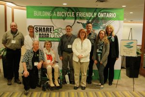 "Cycling advocates pose for a photo in front of the  ""Share the Road"" backdrop at the Summit."