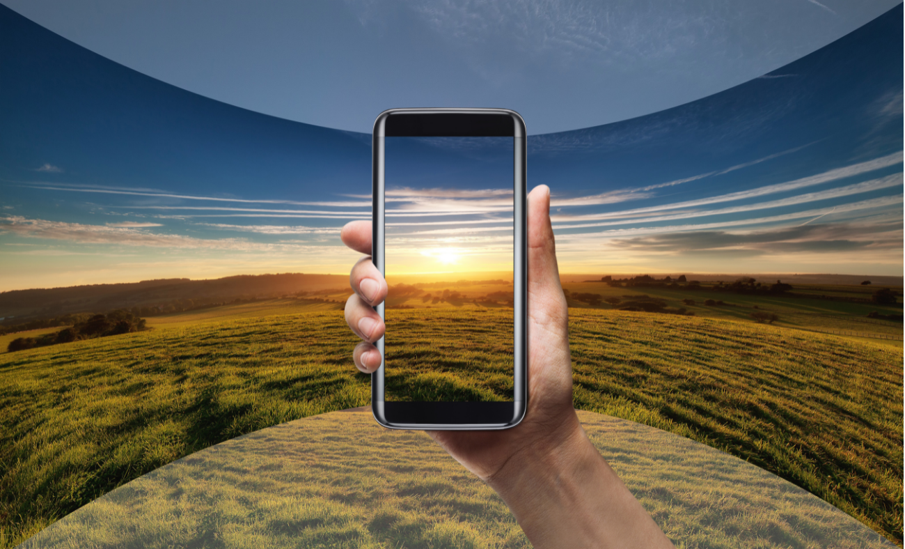Hand holding a mobile phone in front of landscape